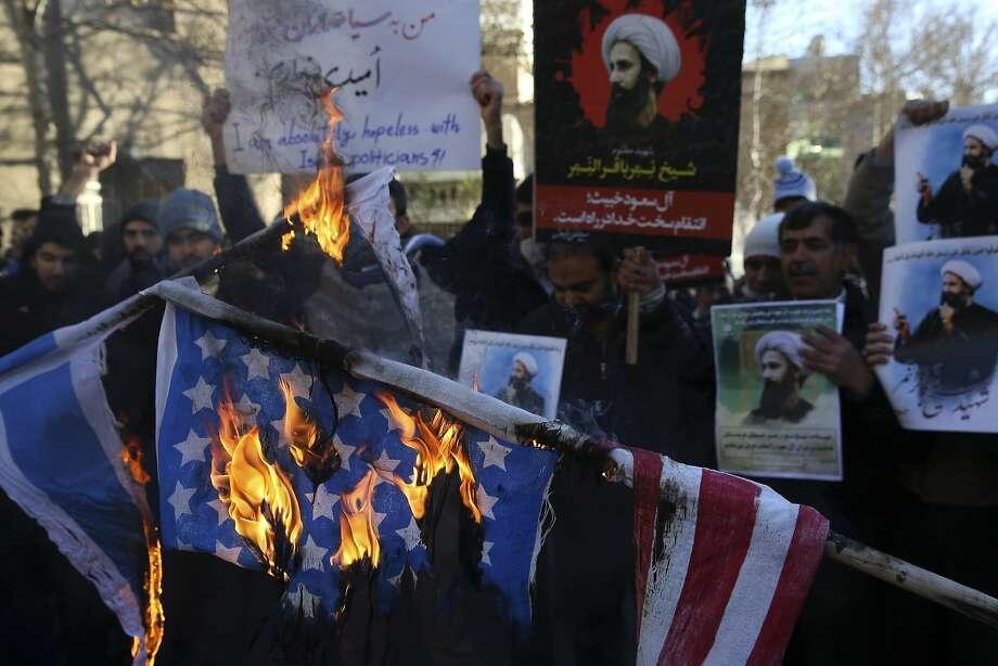 Demonstrators burn U.S. and Israeli flags in front of the Saudi Arabian Embassy in Tehran on Sunday. Photo: Vahid Salemi, Associated Press