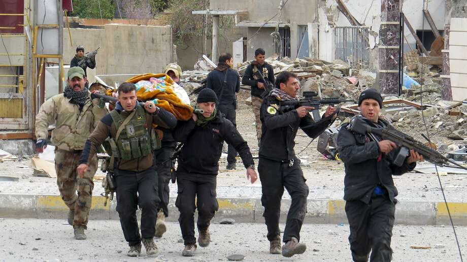 Iraqi government forces carry the body of a comrade Monday during the fight to retake Ramadi. Photo: Str, AFP / Getty Images