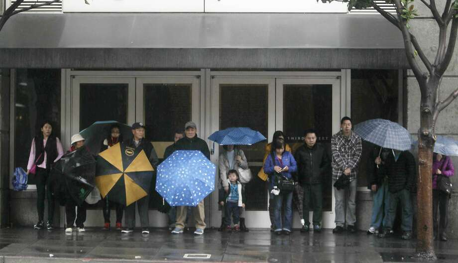 People try to stay out of the rain under an awning at a bus stop on Tuesday, January 5, 2015 in San Francisco, Calif. Photo: Lea Suzuki, The Chronicle