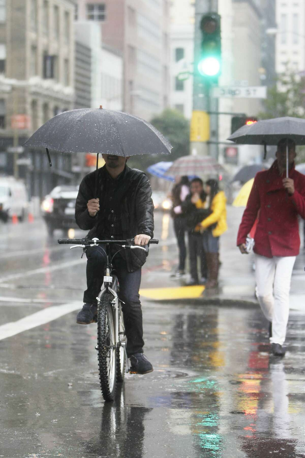 A bicyclist crosses Third Street in the rain under an umbrella on Tuesday, January 5, 2015 in San Francisco, Calif.