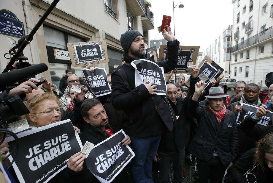 A day after masked gunmen stormed Charlie Hebdo's Paris office last January, journalists wave supportive banners during a minute of silence outside the satirical newspaper's headquarters. Photo: Francois Mori, Associated Press