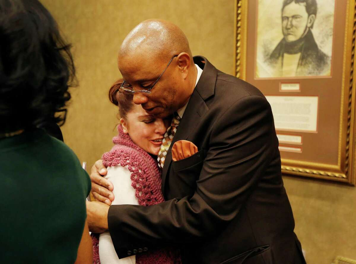 Harris County Precinct One Media Officer, David Ellison hugs Harris County Institute of Forensic Sciences Public Information Officer Tricia Rudisill Bentley after the Commissioners Court meeting Tuesday, Jan. 5, 2016, in Houston. El Franco Lee's chair was draped with a black ribbon as a memorial to his life.