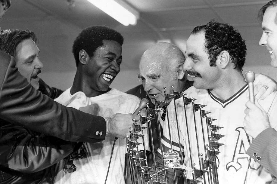 Champagne drips from the face of Oakland Athletics owner Charlie O. Finley, center, as he talks to reporters with players Allan Lewis and Sal Bando, right, in the dressing room in Cincinnati, Ohio, Oct. 22, 1972.  Lewis scored the winning run in the sixth inning off a center field double by Bando to give the A's the World Series victory over the Cincinnati Reds in game seven.  (AP Photo)  Charles Finley celebrates 1972 World Series championship over the Cincinnati Reds with A's player Allan Lewis and Sal Bando (right). Photo: AP