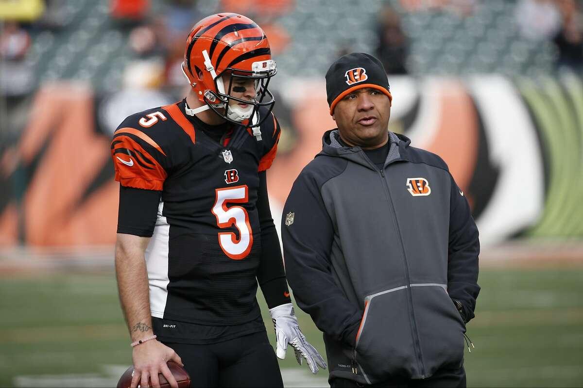 Cincinnati Bengals quarterback AJ McCarron (5) speaks with offensive coordinator Hue Jackson, right, during practice before an NFL football game against the Baltimore Ravens, Sunday, Jan. 3, 2016, in Cincinnati.