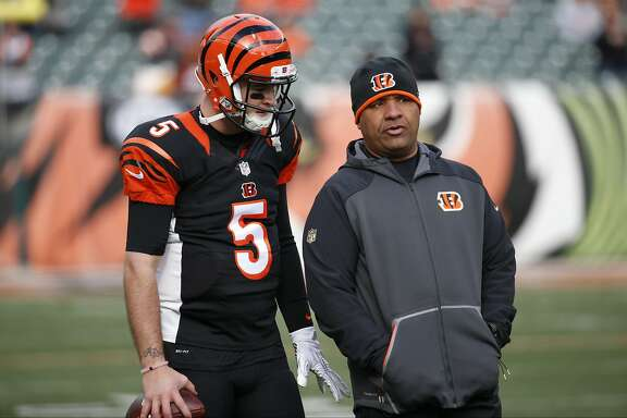 Cincinnati Bengals quarterback AJ McCarron (5) speaks with offensive coordinator Hue Jackson, right, during practice before an NFL football game against the Baltimore Ravens, Sunday, Jan. 3, 2016, in Cincinnati. (AP Photo/Frank Victores)
