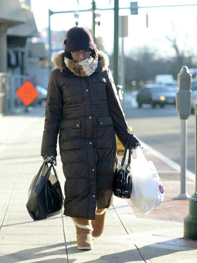Myrtie Boland of Stamford bundles up from the cold weather as she makes her way home from the Stamford Train Station on Tuesday. Photo: Matthew Brown / Hearst Connecticut Media / Stamford Advocate
