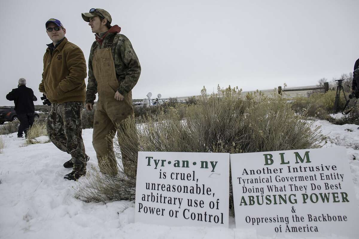 Members of an armed anti-government militia, monitor the entrance to the Malheur National Wildlife Refuge Headquarters near Burns, Oregon January 5, 2016. The occupation of a wildlife refuge by armed protesters in Oregon reflects a decades-old dispute over land rights in the United States, where local communities have increasingly sought to take back federal land. While the standoff in rural Oregon was prompted by the jailing of two ranchers convicted of arson, experts say the issue at the core of the dispute runs much deeper and concerns grazing or timber rights as well as permits to work mines on government land in Western states. AFP PHOTO / ROB KERRROB KERR/AFP/Getty Images