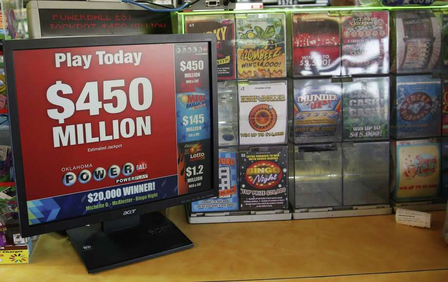 A sign advertising Powerball tickets is pictured next to a display of instant lottery tickets in Oklahoma City. The estimated Powerball jackpot for Wednesday night has soared to $450 million. Photo: Sue Ogrocki /Associated Press / AP