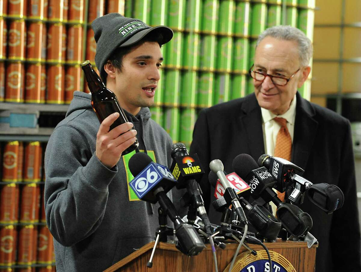 U.S. Senator Charles Schumer, right, listens to Alejandro Del Peral, founder of Nine Pin Ciderworks, explain how the recently passed CIDER Act will help his business and boost the Capital RegionOs and Upstate New YorkOs growing hard cider industry during a press conference at Nine Pin Ciderworks on Tuesday, Jan. 5, 2016 in Albany, N.Y. (Lori Van Buren / Times Union)
