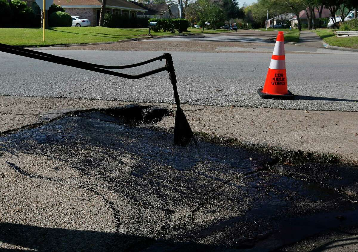Timothy Drones sprays SS-1, an emulsion which helps asphalt adhere to the road, over an area his City of Houston road crew is about to patch at the corner of Belle Park Drive and Bandlon Drive, Tuesday, Jan. 5, 2016, in Houston.