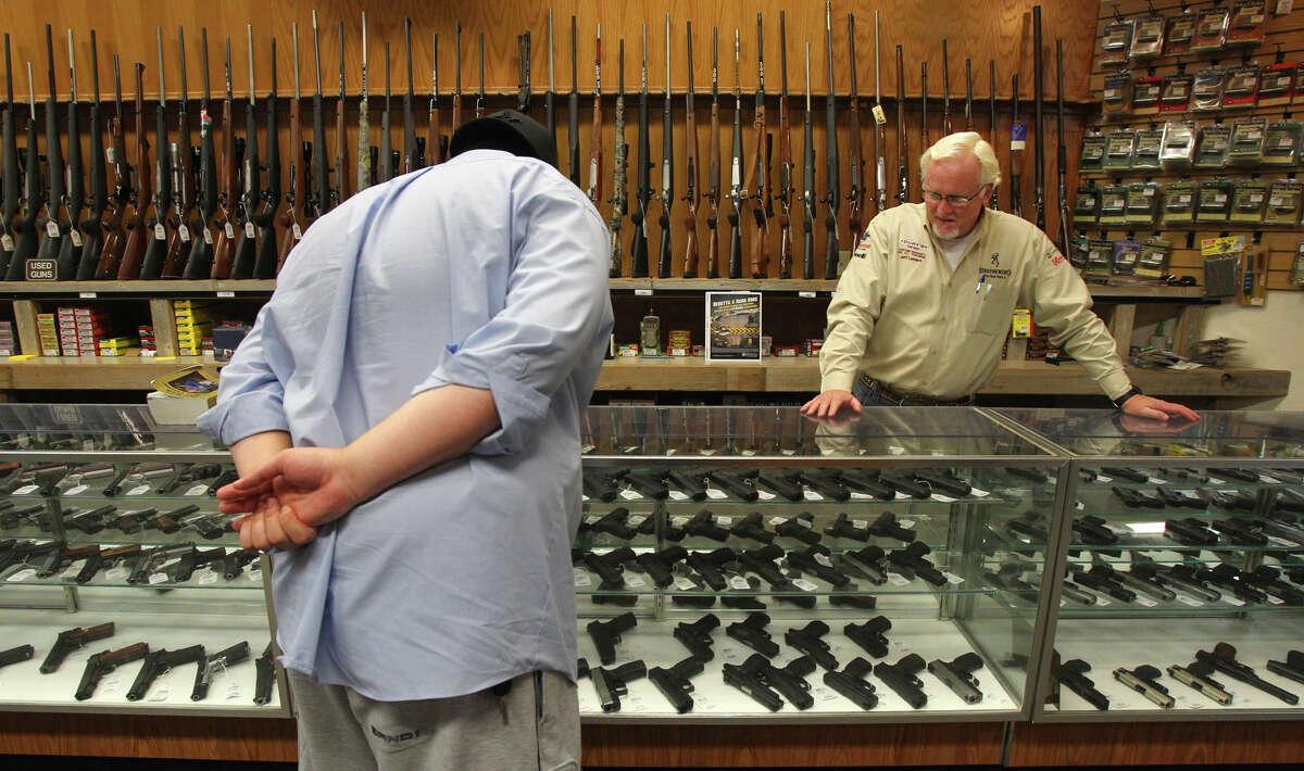 Alex Wilson (left) shops for a pistol with the help of Dury's Gun Shop employee Jeff Leonard (facing) Wednesday July 25, 2012. Dury's sells rifles, pistols and ammunition. John Davenport/San Antonio Express-News