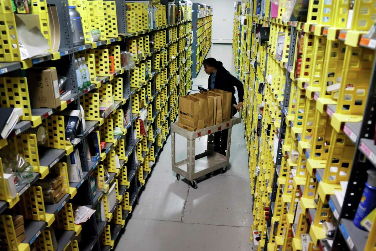 Amazon employee Alicia Jackson hunts for items to ship last month at a company warehouse in New York.