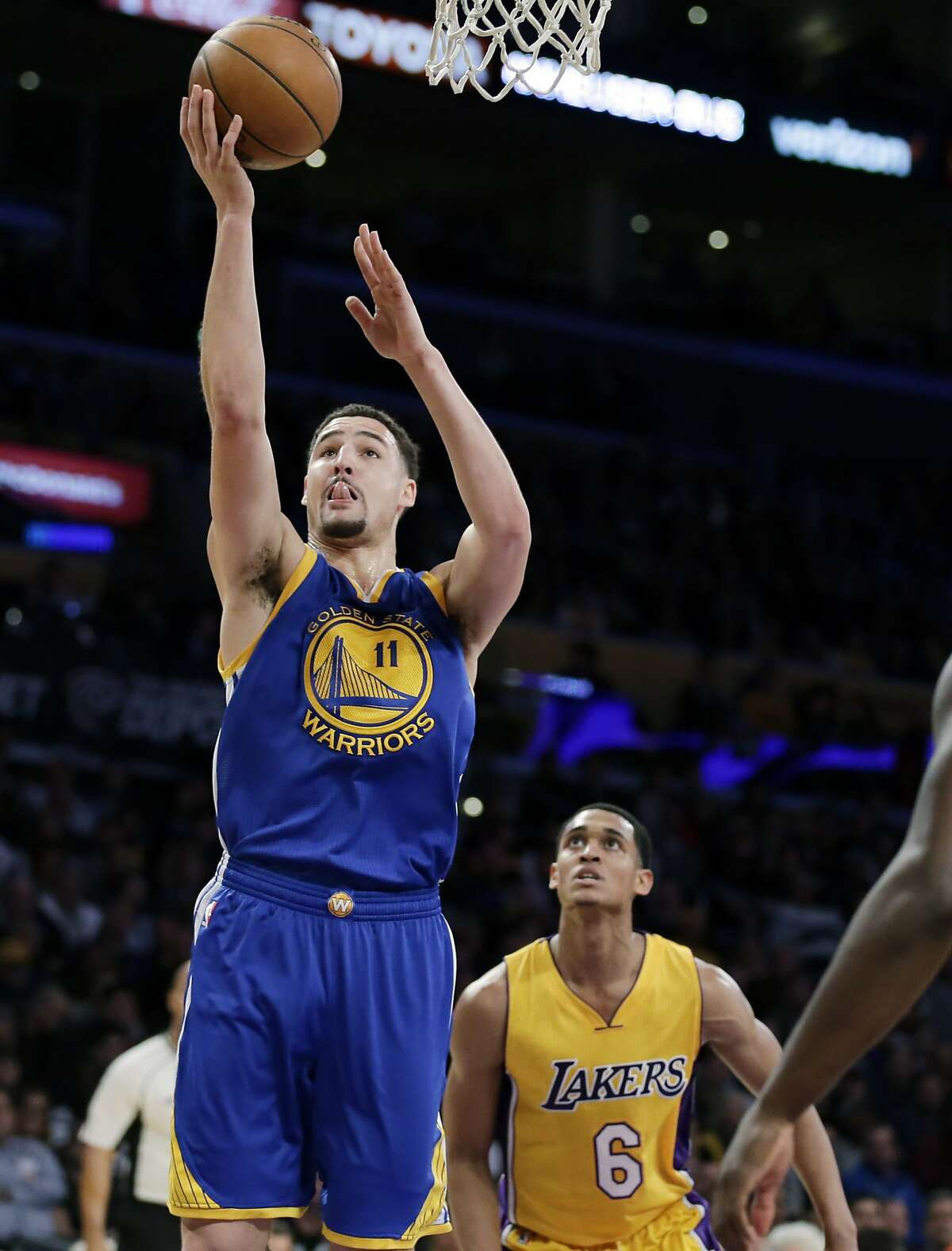 Golden State Warriors guard Klay Thompson, left, shoots as Los Angeles Lakers guard Jordan Clarkson watches during the first half of an NBA basketball game in Los Angeles, Tuesday, Jan. 5, 2016.