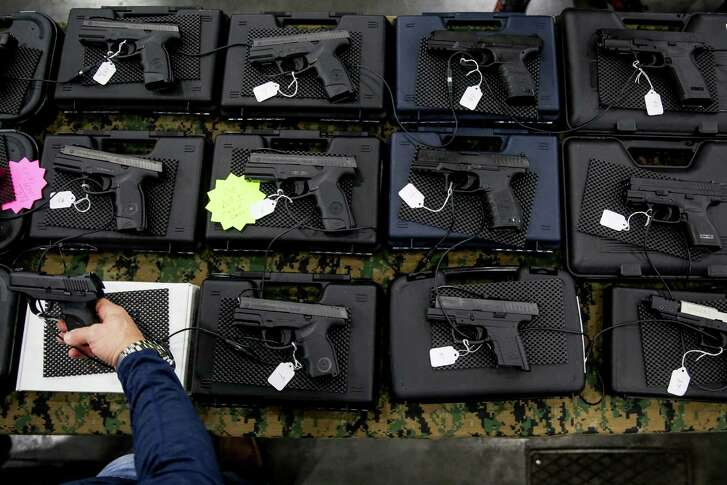 A visitor to the High Caliber Gun and Knife Show at the George R. Brown Convention Center holds a handgun at the Starnes Company Guns booth Saturday, Jan. 2, 2016, in Houston.