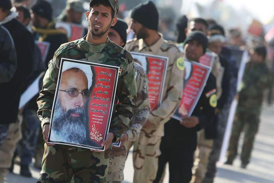 TOPSHOT - Iraqi Shiite members of the Popular Mobilisation units hold portraits of prominent Shiite Muslim cleric Nimr al-Nimr during a demonstration against his execution by Saudi authorities, on January 6, 2016, in the holy Shiite city of Karbala. Nimr was a charismatic religious leader who delivered fiery speeches demanding more rights for his minority in the Sunni-ruled kingdom. His execution led to Shiite protests in several Muslim countries and attacks on Saudi diplomatic missions in Riyadh's regional rival Tehran. AFP PHOTO / MOHAMMED SAWAF / AFP / MOHAMMED SAWAFMOHAMMED SAWAF/AFP/Getty Images Photo: Mohammed Sawaf, AFP / Getty Images