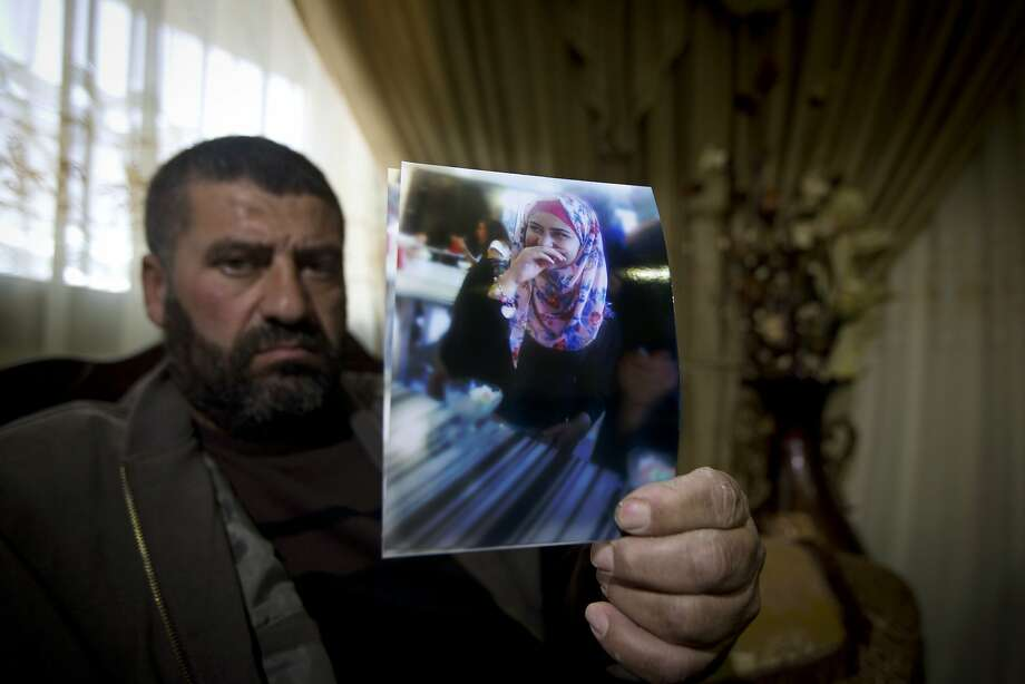 Ramiz Hassoneh holds a photo of his daughter, Maram, in the West Bank city of Nablus. Maram, a top university English student, was killed when she tried to stab Israeli soldiers. Photo: Majdi Mohammed, Associated Press