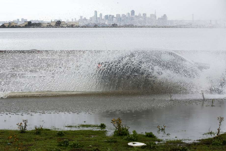 A car drives through a puddle on a rainy day in Alameda, California, with the San Francisco skyline behind it on Wednesday, Jan. 6, 2016. Photo: Connor Radnovich, The Chronicle