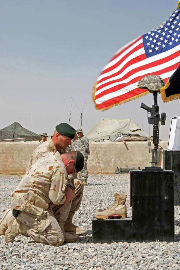 "Dan O'Brien's ""The Body of an American"" is at Hartford Stage. The true story was inspired by a wartime photo taken by photojournalist Paul Watson. Another of his photos is seen here, showing soldiers honoring a fallen comrade in Kandahar, Afghanistan. The play is directed by Jo Bonney and features Michael Crane and Michael Cumpsty. Photo: Paul Watson / Contributed Photo / The News-Times Contributed"