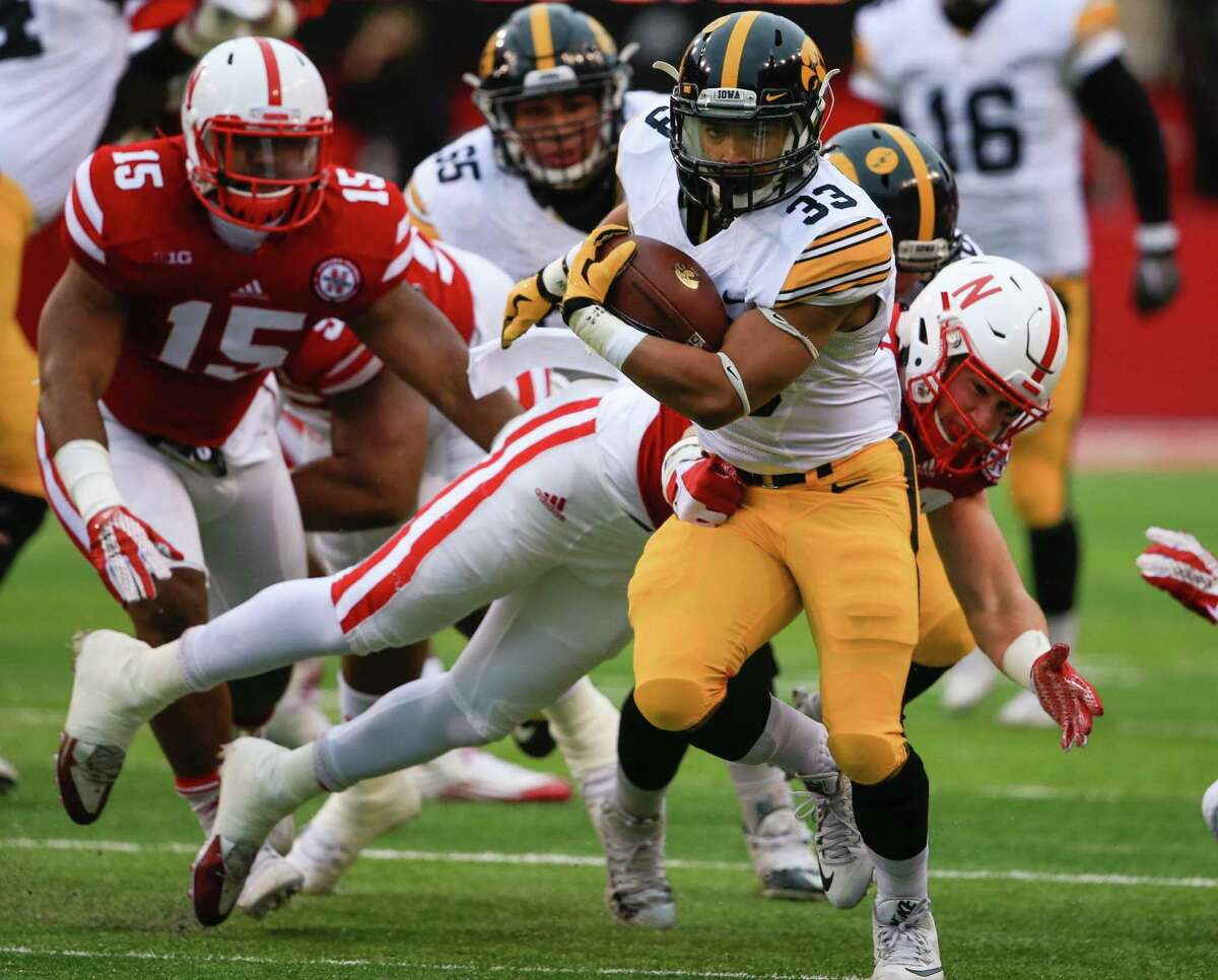 Iowa running back Jordan Canzeri (33) breaks a tackle by Nebraska linebacker Chris Weber (49) during the first half of an NCAA college football game in Lincoln, Neb., Friday, Nov. 27, 2015. (AP Photo/Nati Harnik) ORG XMIT: MER2015113022194652