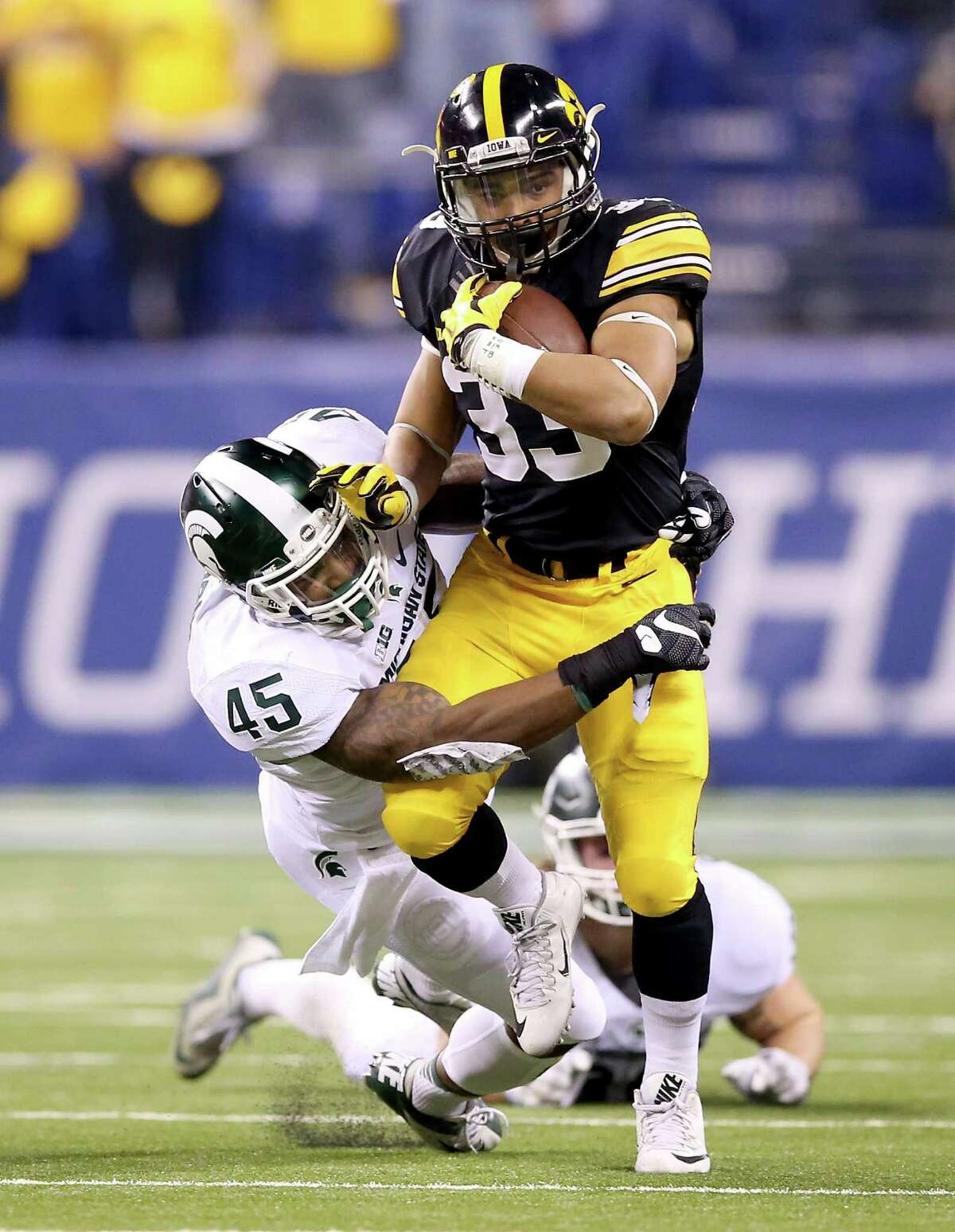 INDIANAPOLIS, IN - DECEMBER 05: Darien Harris #45 of the Michigan State Spartans brings down Jordan Canzeri #33 of the Iowa Hawkeyes in the Big Ten Championship at Lucas Oil Stadium on December 5, 2015 in Indianapolis, Indiana. (Photo by Andy Lyons/Getty Images) ORG XMIT: 587174801