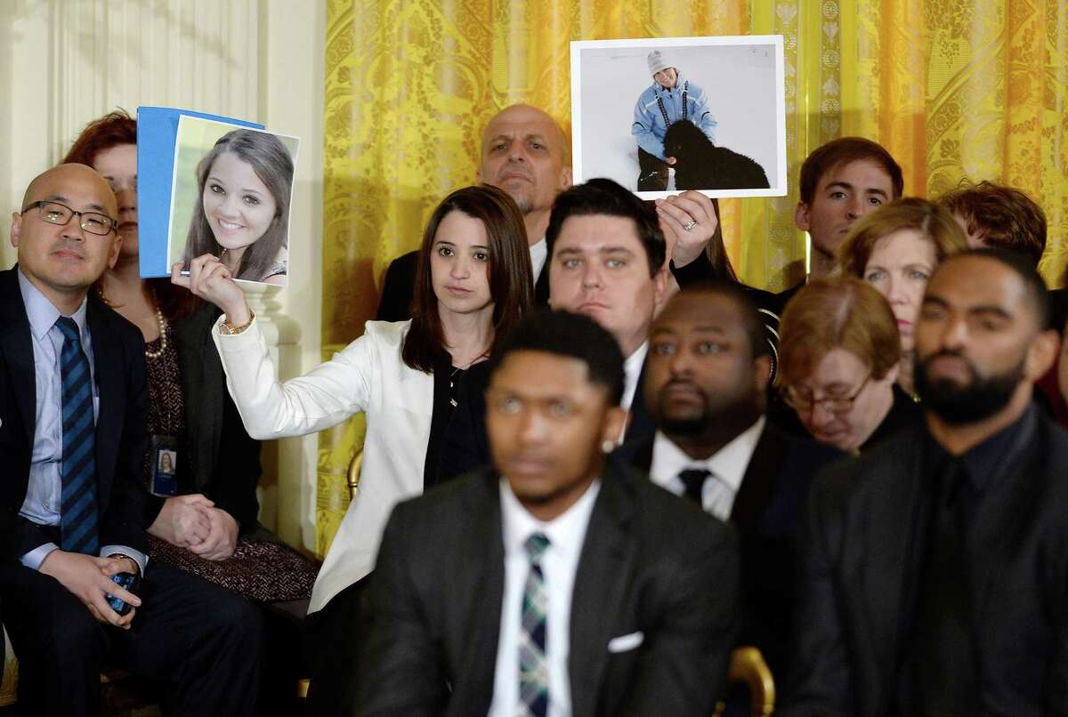 Carlee Soto, left, holding a photo of her sister, slain Sandy Hook Elementary School teacher, Vicki Soto, joins other guests as they hold up images of victims of gun violence. U.S. President Barack Obama delivered remarks about his efforts to increase federal gun control in the East Room of the White House January 5, 2016 in Washington, DC. Without approval from Congress, Obama is sidestepping the legislative process with executive actions to expand background checks for some firearm purchases and step up federal enforcement of existing gun laws.