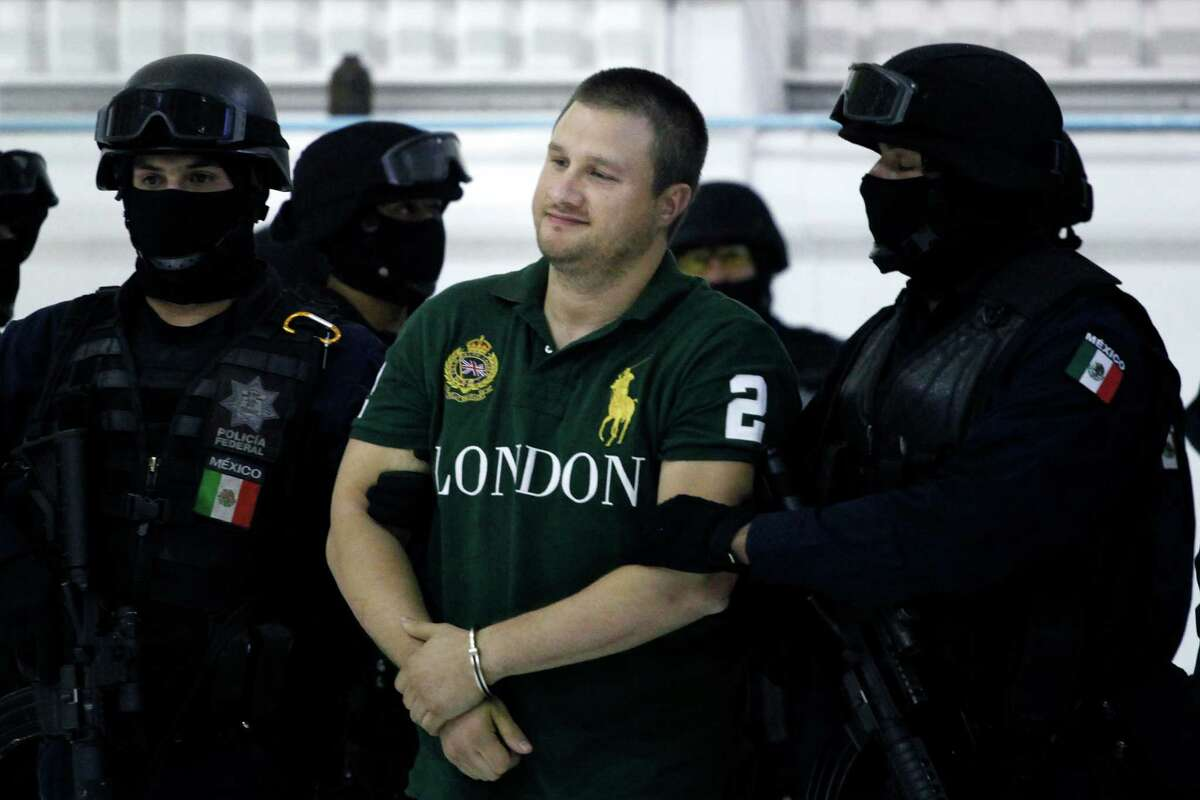 """Federal police stand guard by Texas-born kingpin Edgar Valdez Villarreal, alias """"the Barbie,"""" center, during his presentation to the press in Mexico City, Tuesday Aug. 31, 2010. Valdez, who was captured on Monday by federal police, faces drug trafficking charges in the U.S. and has been blamed for a vicious turf war that has included bodies hung from bridges and shootouts in central Mexico. (AP Photo/Alexandre Meneghini)"""