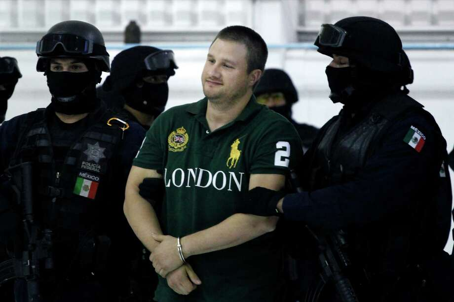 """Federal police stand guard by Texas-born kingpin Edgar Valdez Villarreal, alias """"the Barbie,"""" center, during his presentation to the press in Mexico City, Tuesday Aug. 31, 2010. Valdez, who was captured on Monday by federal police, faces drug trafficking charges in the U.S. and has been blamed for a vicious turf war that has included bodies hung from bridges and shootouts in central Mexico. (AP Photo/Alexandre Meneghini) Photo: Alexandre Meneghini, STF / ASSOCIATED PRESS / AP2010"""