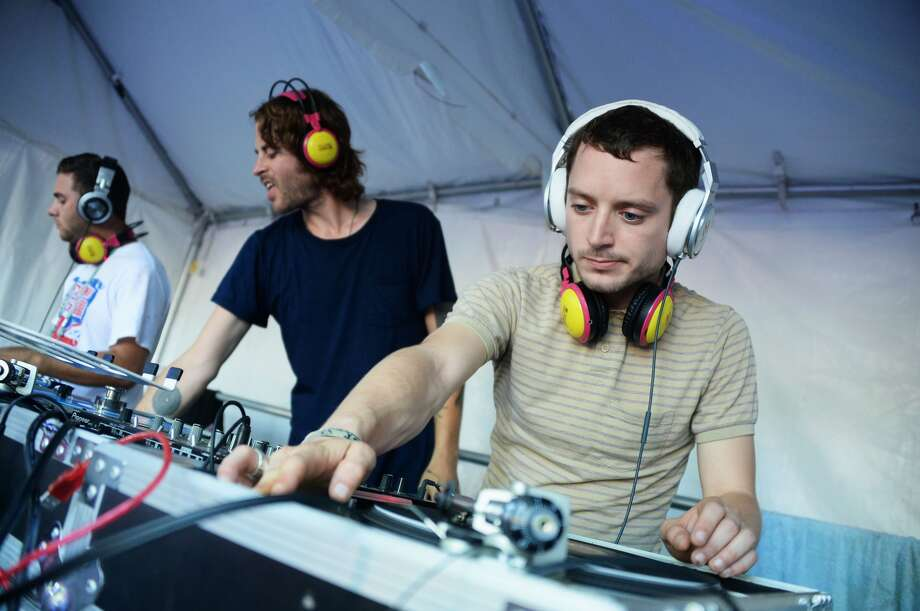 Zach Cowie (L) and Elijah Wood spin onstage at the Firefly Music Festival at The Woodlands of Dover International Speedway on June 23, 2013 in Dover, Delaware. (Photo by Theo Wargo/Getty Images for Firefly Music Festival)