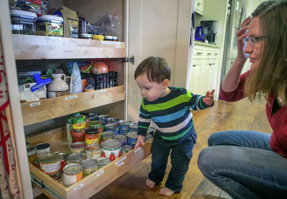 Alicia Marmaros, right, and her 19-month old son Aaron, check the canned/jarred food drawer in her kitchen pantry closet at her home in Los Altos, California. The canned/jarred food was placed lower so that they would be easy to access and identify. Photo: LiPo Ching /McClatchy-Tribune News Service / San Jose Mercury News