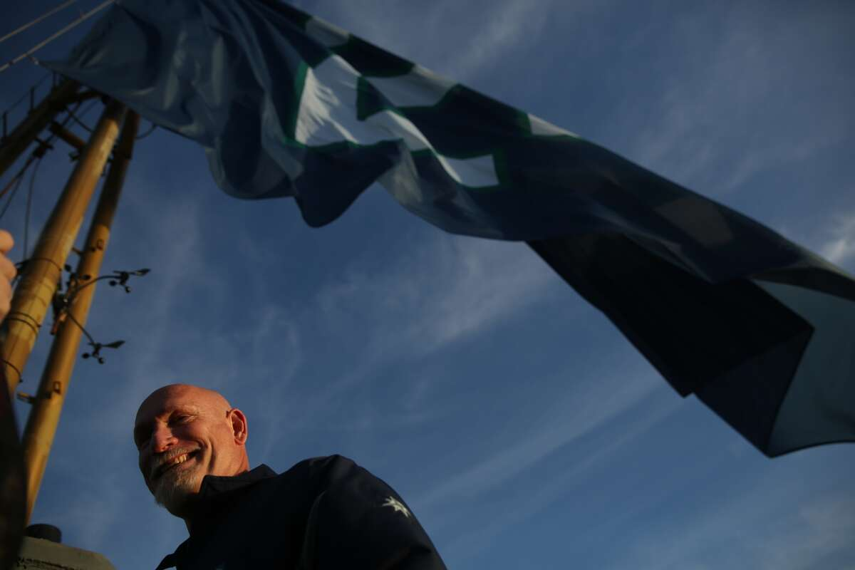 Jay Buhner, former teammate of Ken Griffey Jr., raises a flag of Griffey's number on top of the Space Needle on Wednesday, Jan. 6, 2015.