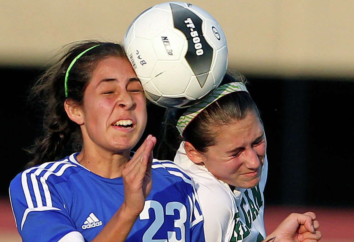 MacArthur's Stephanie Figueroa (23) and Reagan's Ashley Long crunch a header together in a girls soccer playoff game at Blossom Soccer Stadium on April 10, 2012.
