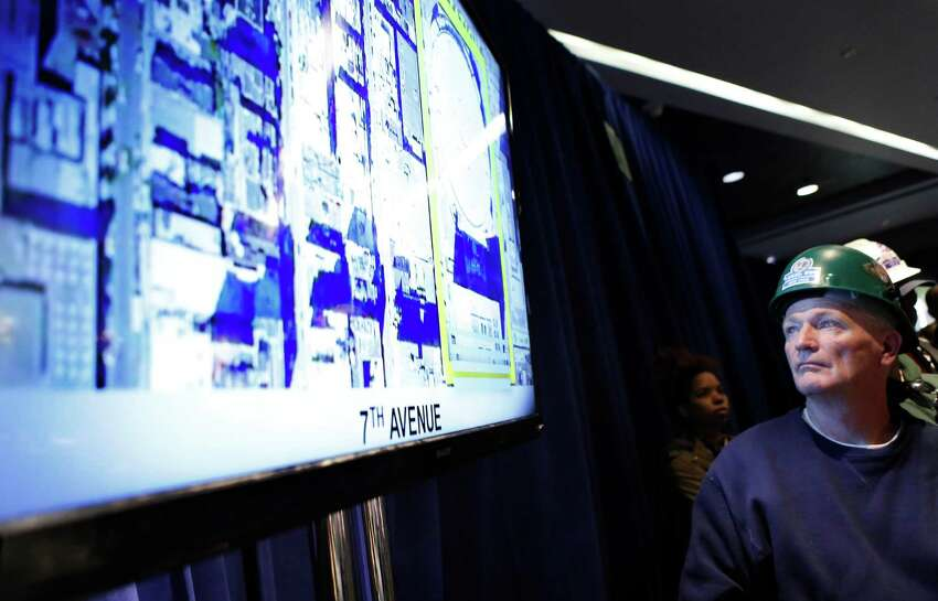 A construction worker looks at plans for the overhaul of Pennsylvania Station during a press conference led by New York Gov. Andrew Cuomo, Wednesday, Jan. 6, 2016, in New York. Cuomo announced that work will commence immediately on the overhaul of Pennsylvania Station at Madison Square Garden, Wednesday, Jan. 6, 2016, in New York. (AP Photo/Kathy Willens)