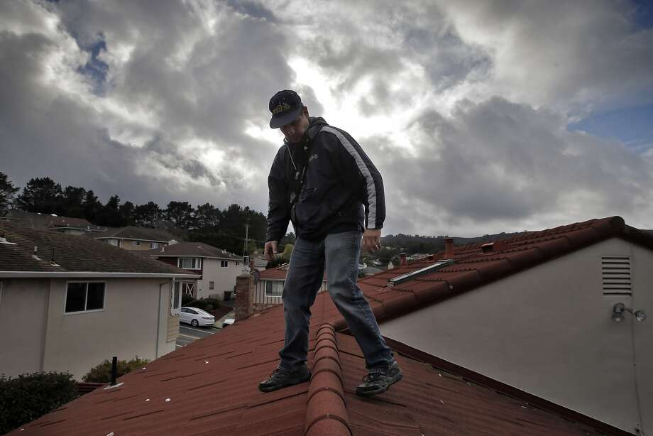 Ricardo Molina of Mr. Roofers, walks back down the roof after he checked the roof of Novella Jefferson's home in San Bruno, Calif., on Wednesday, January 6, 2016.  Some businesses have seen up uptick in work due to the arrival of storms from El Niño. Photo: Carlos Avila Gonzalez, The Chronicle