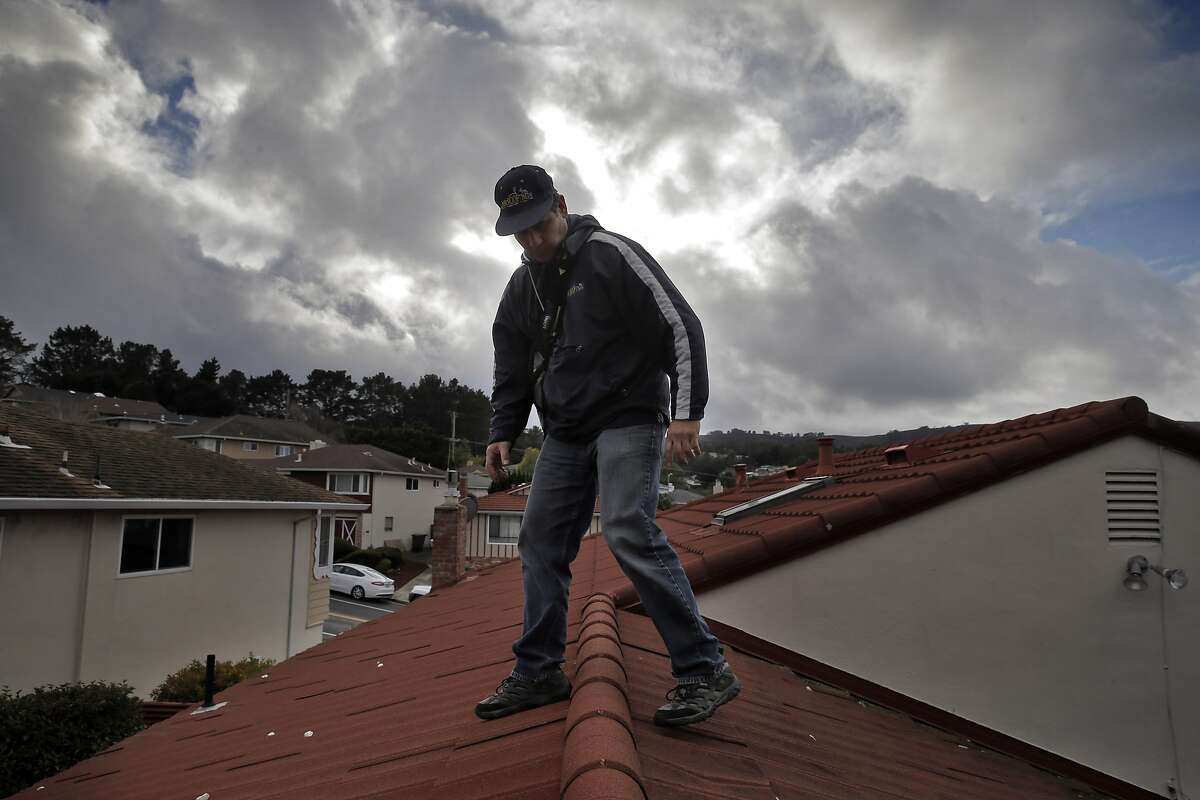 Ricardo Molina of Mr. Roofers, walks back down the roof after he checked the roof of Novella Jefferson's home in San Bruno, Calif., on Wednesday, January 6, 2016. Some businesses have seen up uptick in work due to the arrival of storms from El Niño.