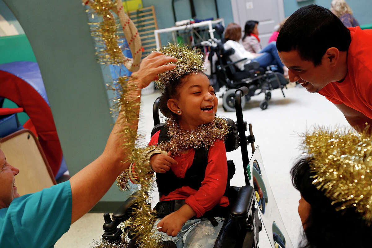 Maliah Salas-Cook, 6, gets ready for the Christmas party with physical therapist Beth McMahon, left, and Dion Ruiz at TEAMability in San Antonio on Dec. 9, 2015.