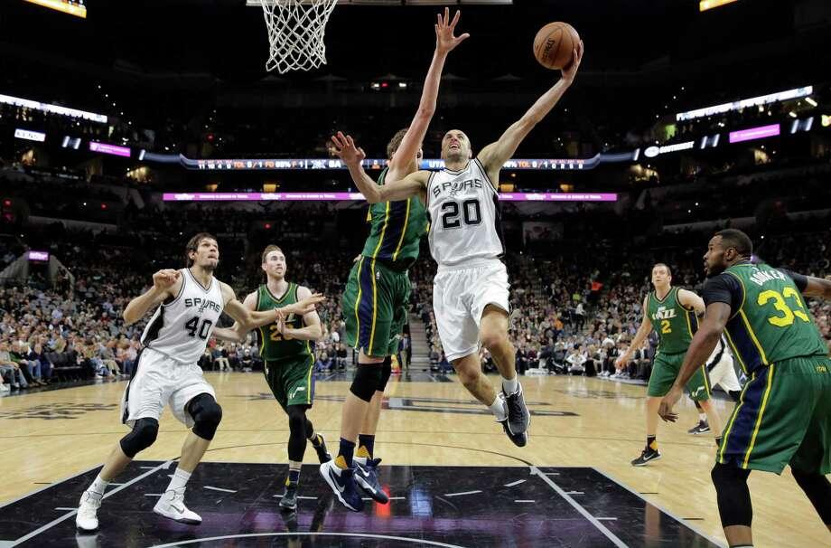 San Antonio Spurs guard Manu Ginobili (20) drives to the basket around Utah Jazz center Tibor Pleiss (21) during the first half of an NBA basketball game, Wednesday, Jan. 6, 2016, in San Antonio. Photo: Eric Gay, AP / AP