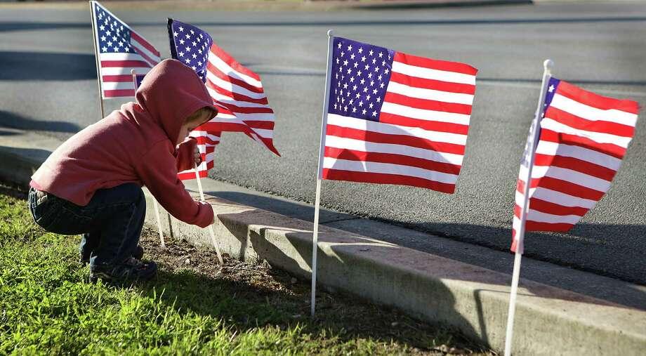 Micah Schaefer, 2, plants flags before the procession for Airman Michael A. Cinco leaves Joint Base San Antonio-Randolph. Photo: Photos By Bob Owen /San Antonio Express-News / San Antonio Express-News