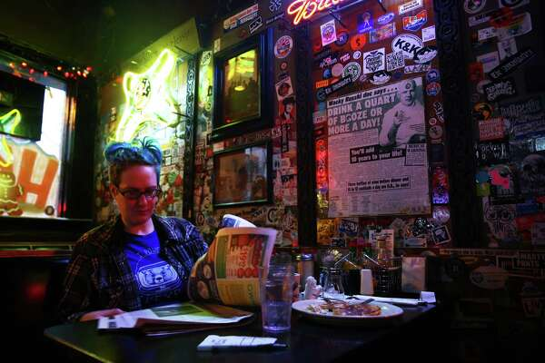 Kim Klenn reads the paper over lunch at the 5 Point Cafe in Belltown, Dec. 15, 2015.