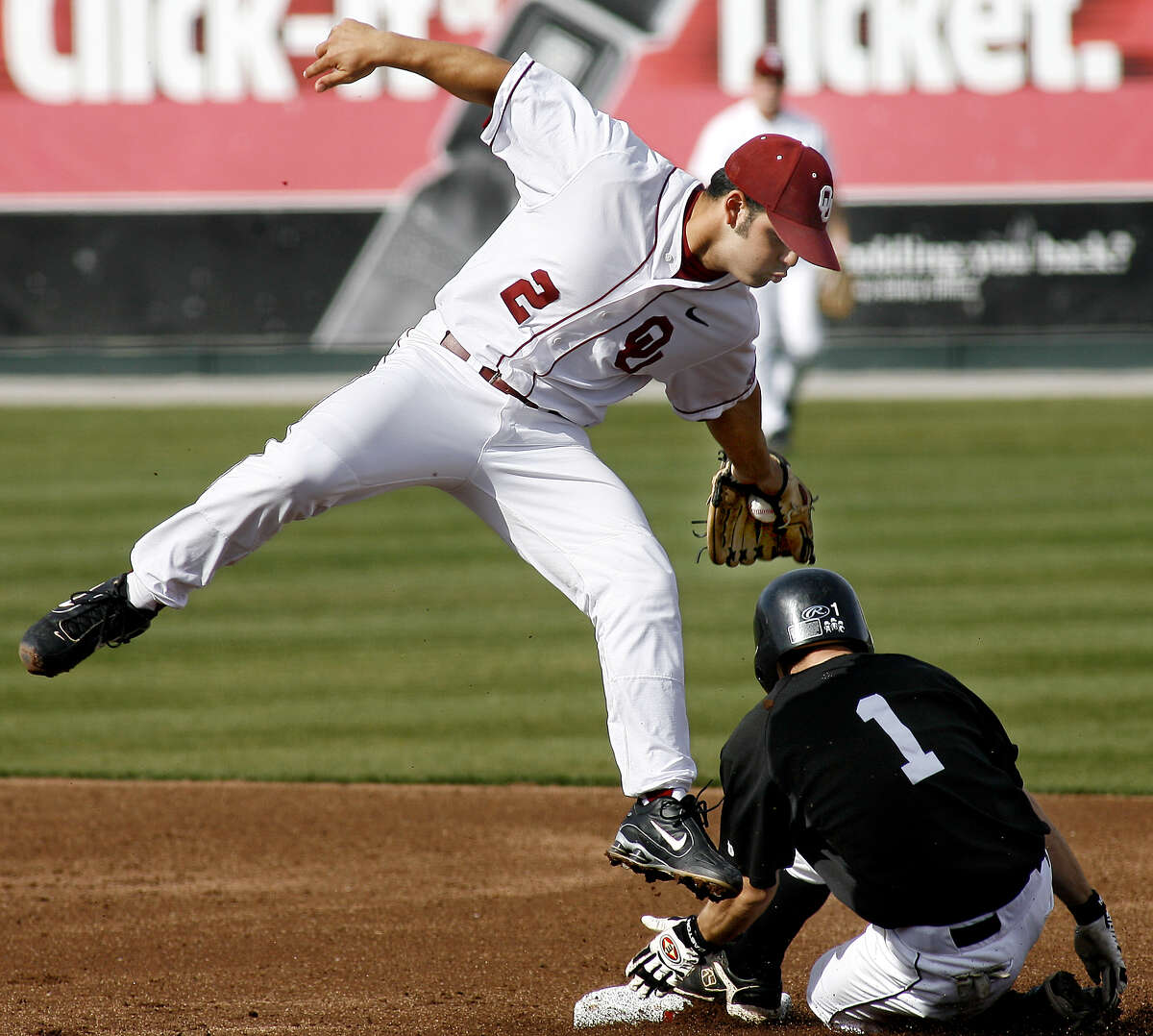 Wichita State outfielder Kenny Waddell (1) slides under the tag of Oklahoma second baseman Aaron Reza (2) in a baseball game Tuesday, Feb. 28, 2006, in Norman, Okla.