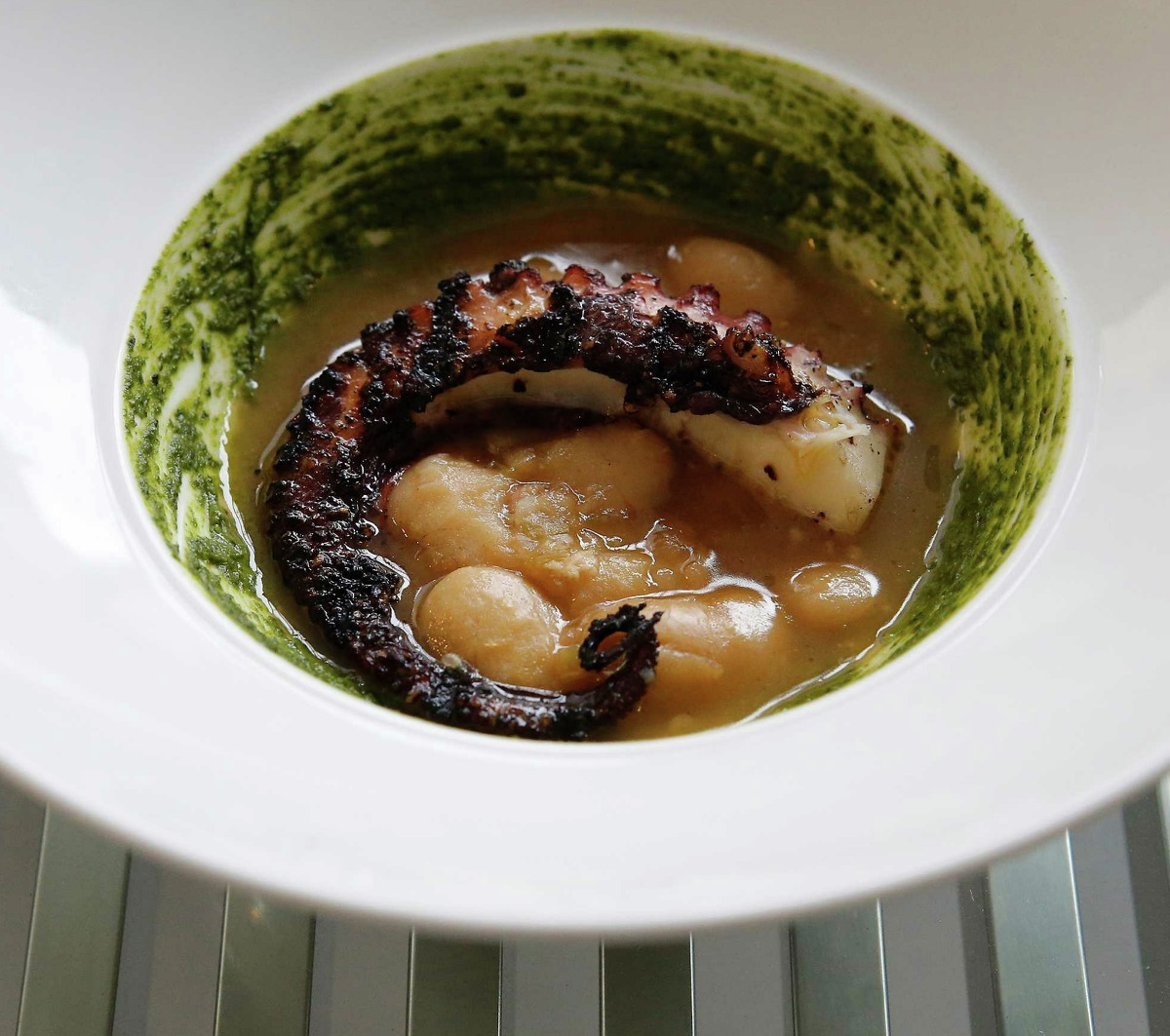 The tender chargrilled Spanish octopus is served with braised corona beans and a basil pistou.