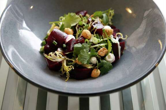 Charred beets with crème fraîche, malted peanuts, cilantro, curly endive and preserved lemon.