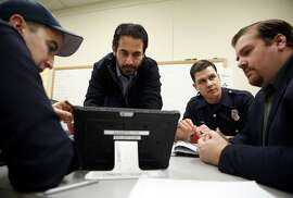 Jonathon Feit (center) works on a tablet as Patrick Corder (left) points out aspects of the program they're working on while Christian Witt (right) listens to Dave Wills during a community paramedicine meeting at City Hall West in Alameda, California, on Wednesday, Jan. 6, 2016.