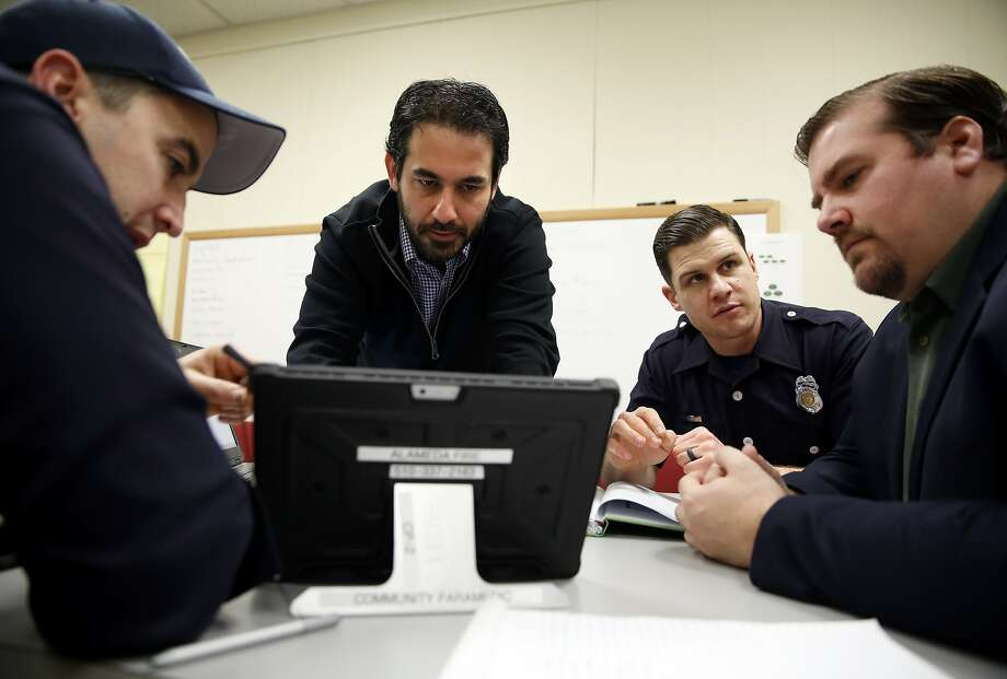 Jonathon Feit (center) works on a tablet as Patrick Corder (left) points out aspects of the program they're working on while Christian Witt (right) listens to Dave Wills during a community paramedicine meeting at City Hall West in Alameda, California, on Wednesday, Jan. 6, 2016. Photo: Connor Radnovich, The Chronicle