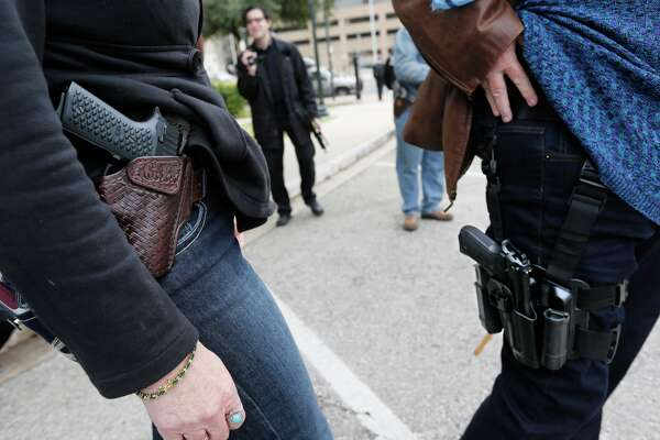 Two women compare handgun holsters during an open carry rally at the Texas State Capitol in Austin, Texas. On January 1, 2016, the open carry law took effect in Texas, and 2nd Amendment activists held an open carry rally at the Texas state capitol on January 1, 2016 in Austin, Texas.