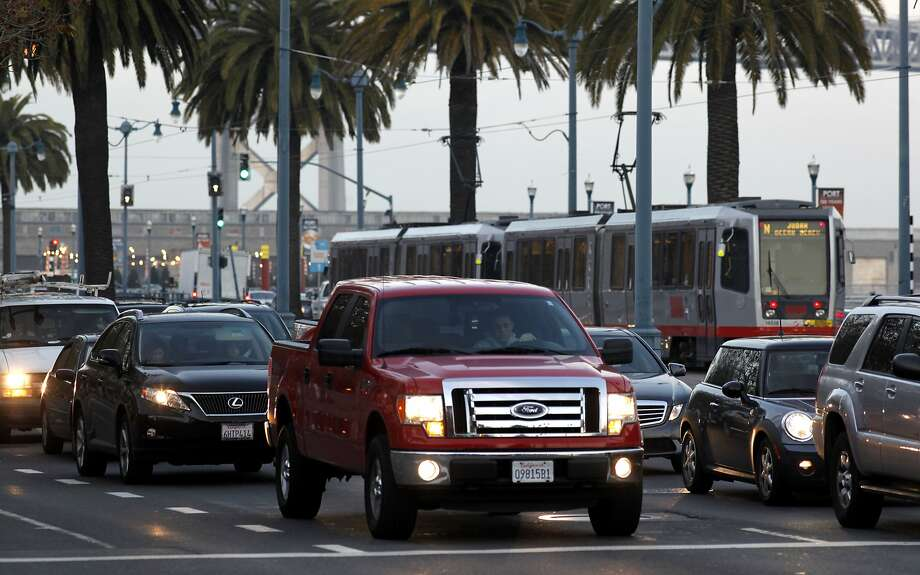 A streetcar passes stopped traffic along the Embarcadero, where southbound lanes will be closed to traffic during Super Bowl City. Photo: Michael Macor, The Chronicle