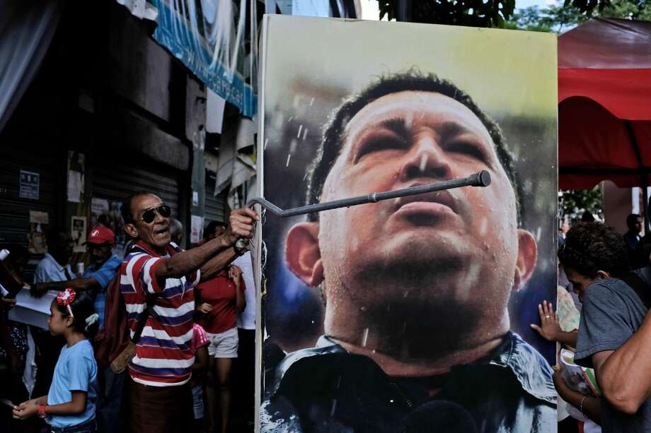 January 16: A Chavista screams at opposition lawmakers beside an image of Chávez removed from Venezuela's parliament building. Photo: Fernando Llano, Associated Press