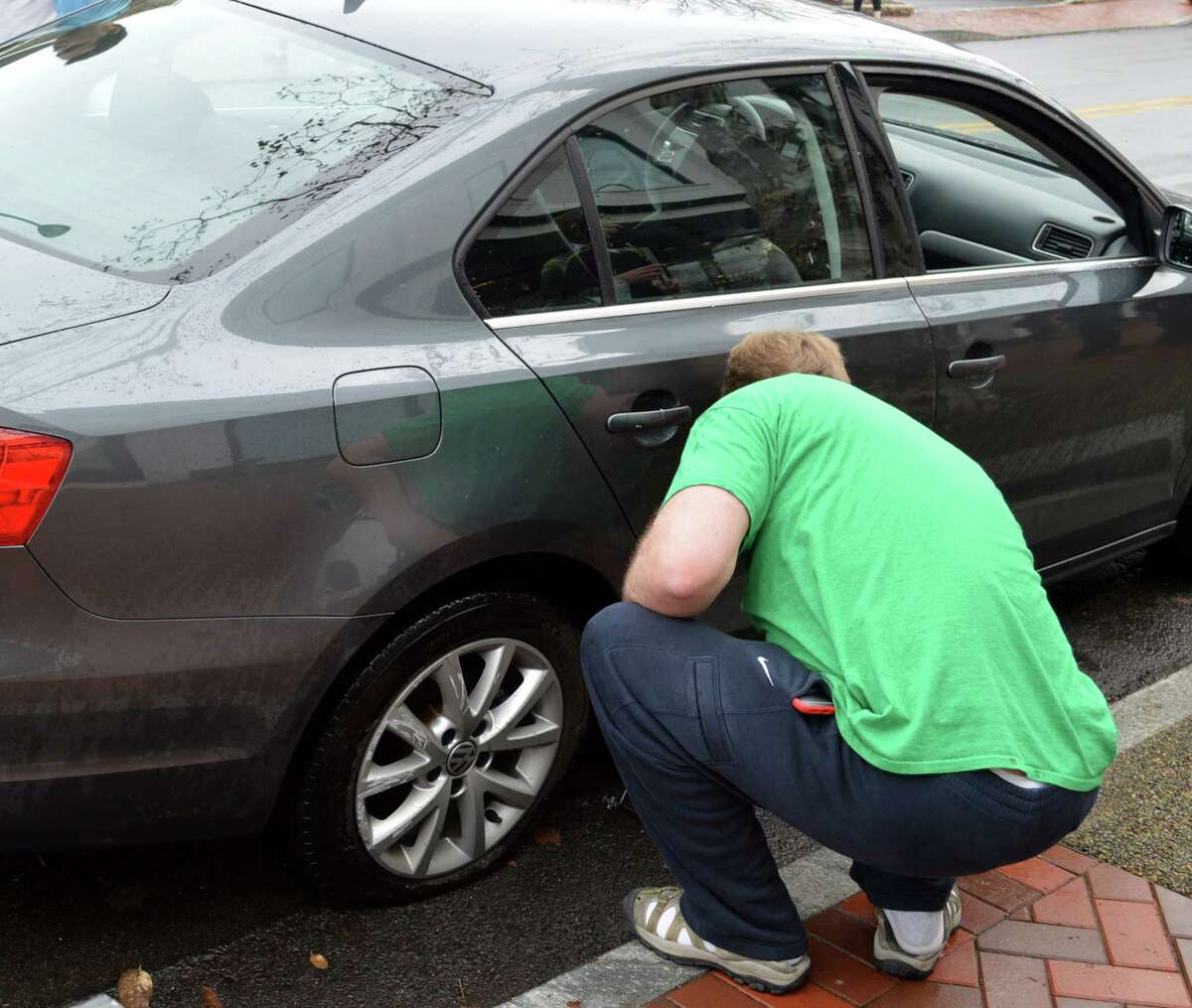 Robert Tupper of Wilton inspects the flat tire he suffered when his tire was gashed by Main Street's new sharp-edged curbing.