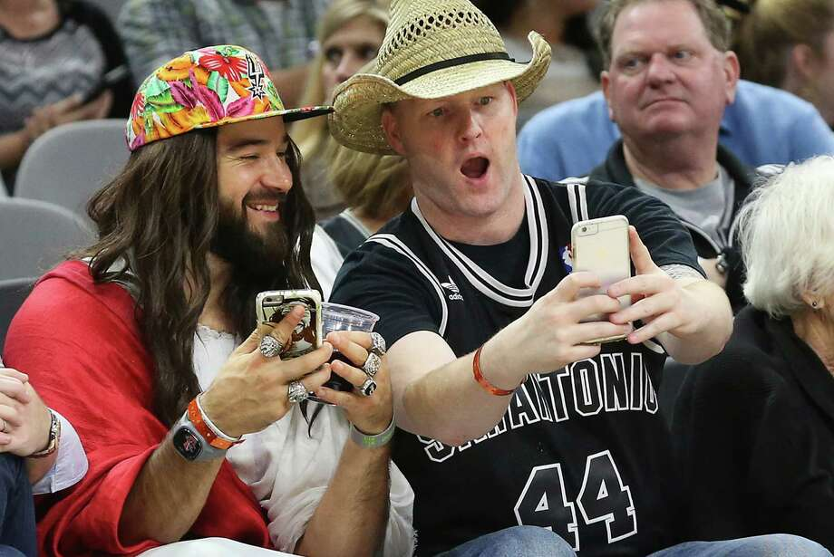 Spurs Jesus takes a selfie with Greg McBride and his $9 hat from San Francisco as the Spurs host Portland at the AT&T Center on Nov. 16, 2015. Photo: Tom Reel /San Antonio Express-news / 2015 SAN ANTONIO EXPRESS-NEWS