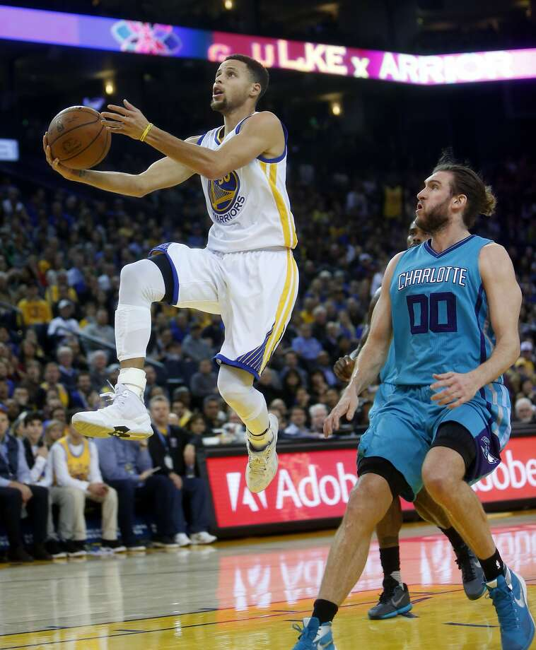 Golden State Warriors' Stephen Curry scores in front of Charlotte Hornets' Spencer Hawes in 2nd quarter during NBA game at Oracle Arena in Oakland, Calif., on Monday, January 4, 2016. Photo: Scott Strazzante, The Chronicle
