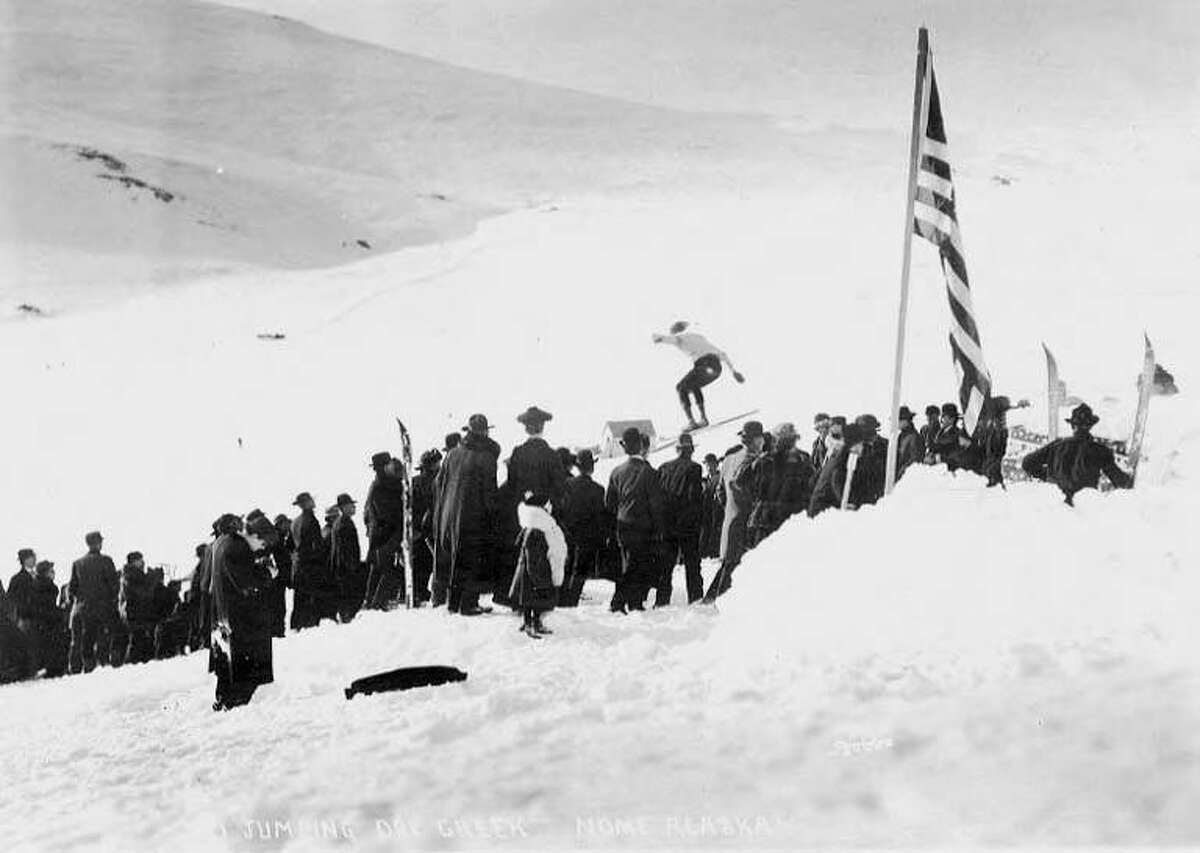 This circa 1905 photo shows a crowd watching a ski jumper at Dry Creek near Nome, Alaska. Nome's first ski club formed in 1901, according to caption information. The ski area was situated on the slope of Anvil Mountain. A natural jump formed along the course of the creek.